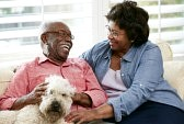 18735709-happy-senior-couple-sitting-on-sofa-with-dog